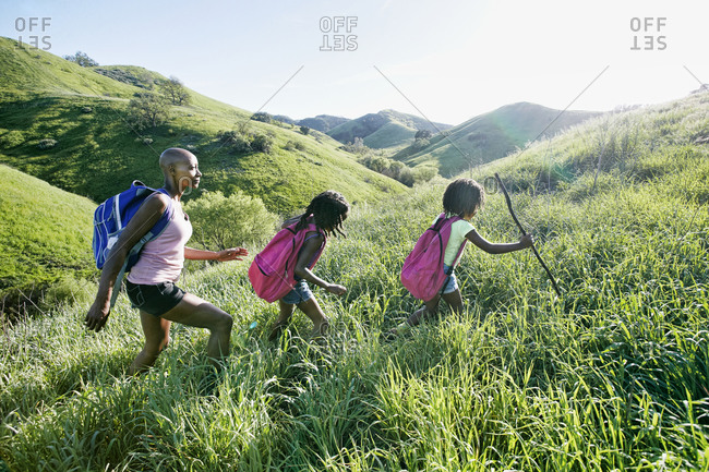 Black mother and daughters walking on rural hillside