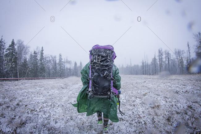 Caucasian hiker standing in frosty field