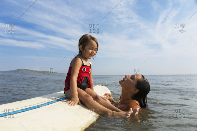 Mother teaching daughter to surf in ocean