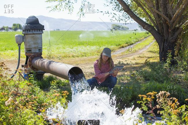 Caucasian farmer checking water pump