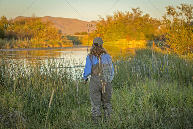 Caucasian woman with fishing gear at river