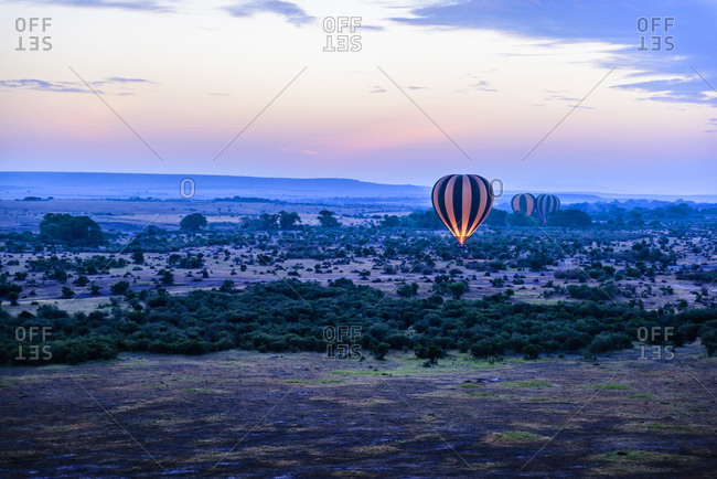 Hot air balloon flying over savanna landscape