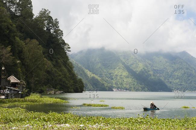Fisherman rowing canoe on still rural lake