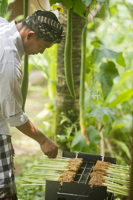 Ubud, Bali, Indonesia - March 24, 2015: Asian chef cooking on grill outdoors