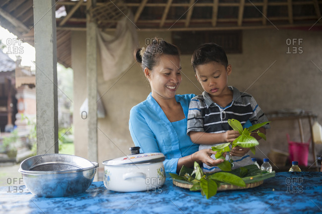 Asian mother and son cooking in outdoor kitchen