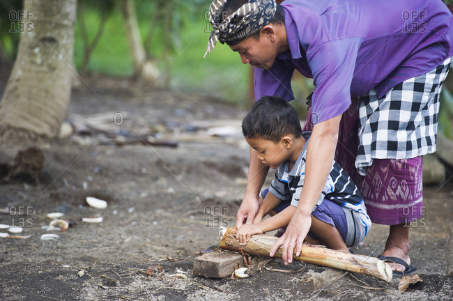 Ubud, Bali, Indonesia - March 27, 2015: Asian father teaching son traditional wood carving