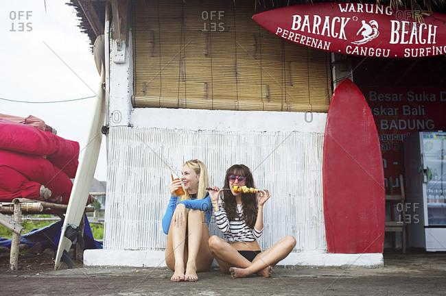 Canggu, Bali, Indonesia - April 23, 2015: Caucasian women eating at surf hut on beach