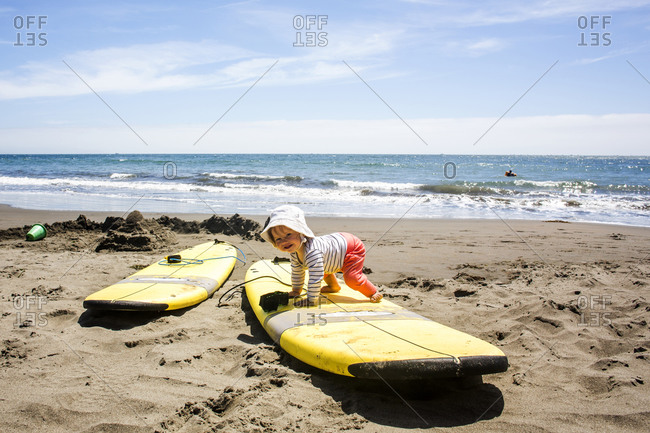 Caucasian baby crawling on surfboard