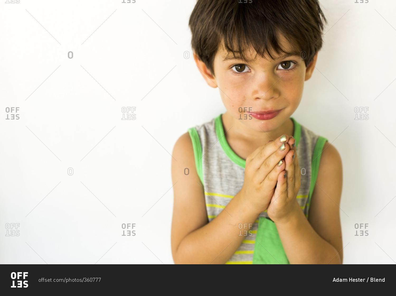 Mixed race boy wearing nail polish stock photo - OFFSET