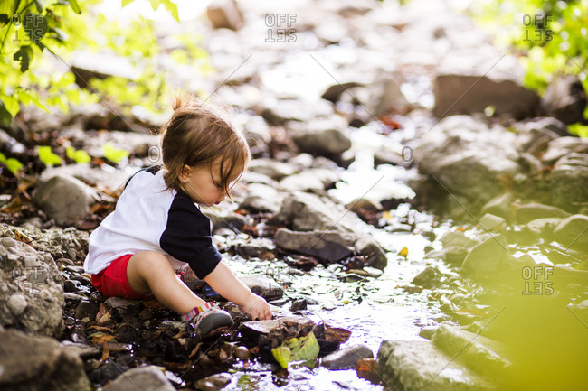 Caucasian baby girl playing in creek