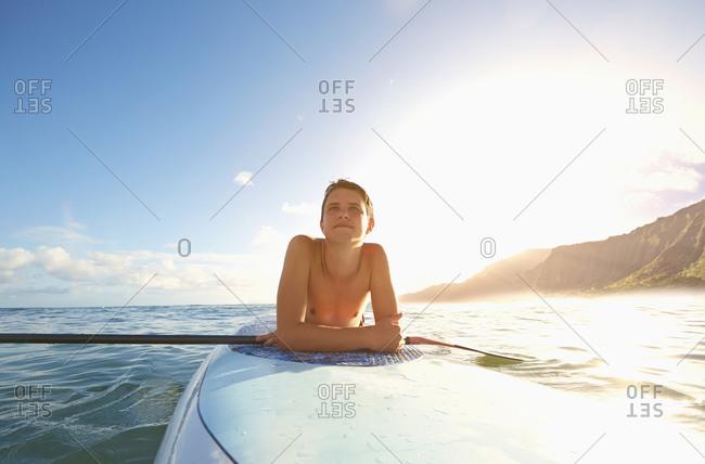 Caucasian teenage boy laying on paddle board in ocean