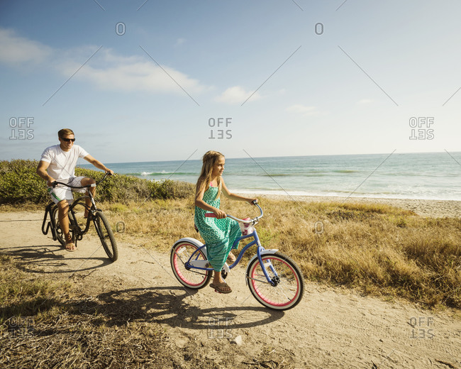 Caucasian father and daughter riding bicycles on beach