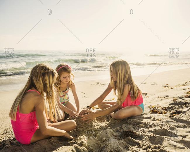 Caucasian sisters building sandcastle on beach
