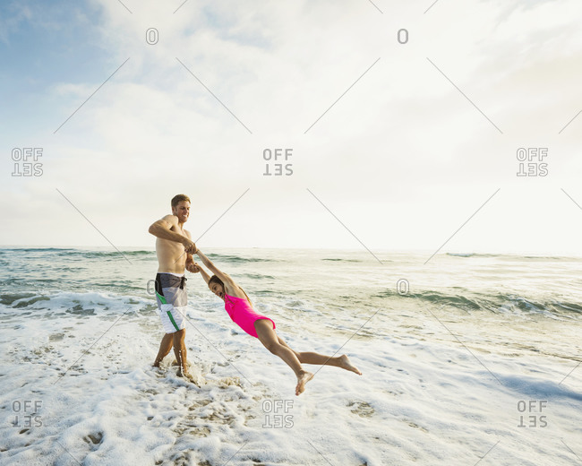 Caucasian father and daughter playing in waves on beach