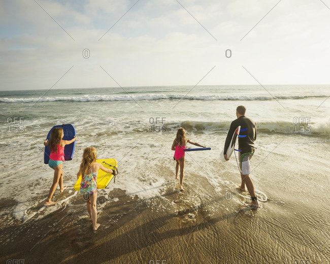 Caucasian father and daughters playing in waves on beach