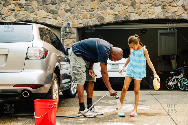 Portland, Oregon, USA - August 22, 2015: Father and daughter washing car