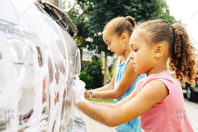 Mixed race sisters washing car