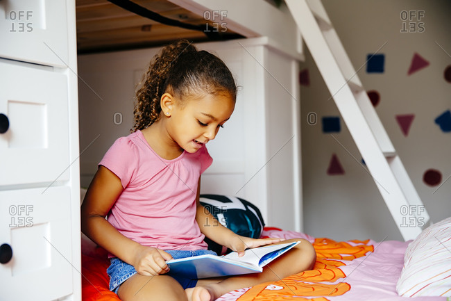 Mixed race girl reading on bed