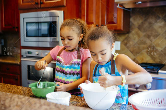 Mixed race sisters cooking in kitchen