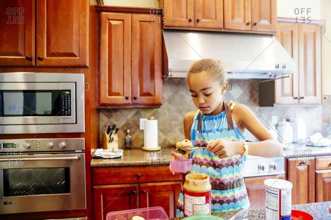 Mixed race girl scooping peanut butter in kitchen