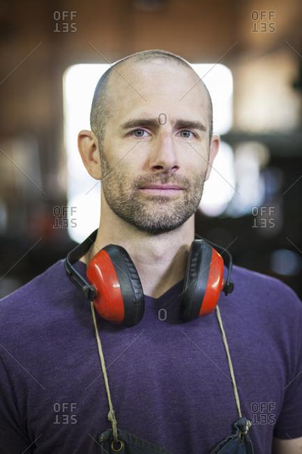 Caucasian worker wearing headphones in factory