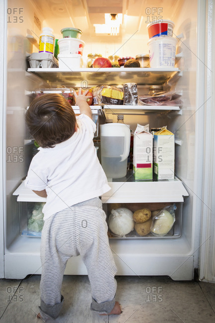 Mixed race baby boy exploring refrigerator