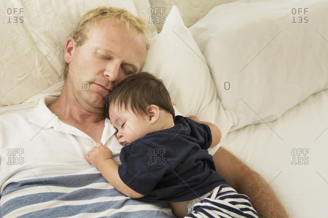 Father and baby son sleeping on bed