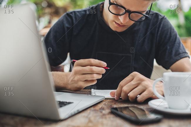 Caucasian man writing in cafe
