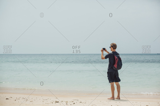 Caucasian man photographing seascape