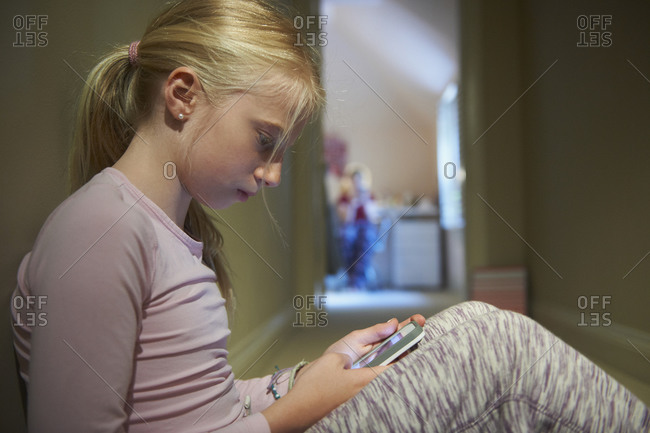 Caucasian girl using cell phone in hallway