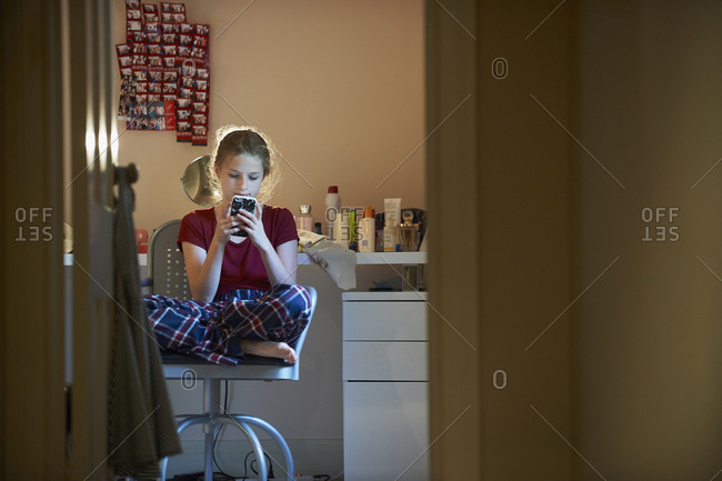 Caucasian girl using cell phone in bedroom