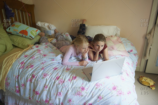 Caucasian sisters using laptop on bed