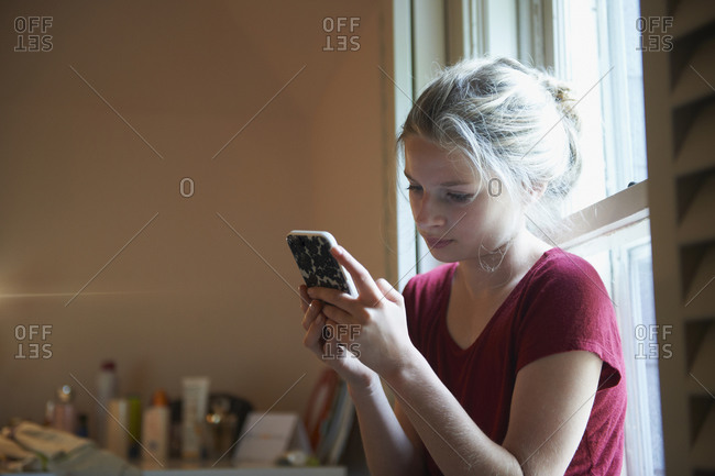 Caucasian girl using cell phone in window