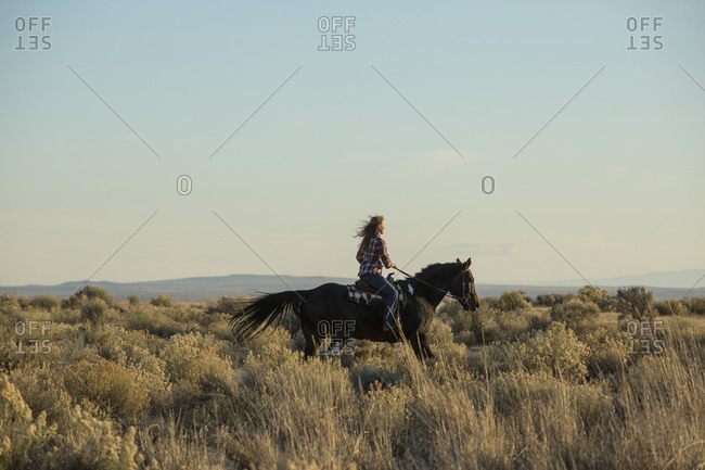 Caucasian woman riding horse in field