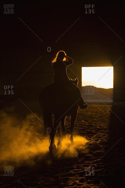 Caucasian woman riding horse in barn