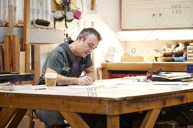 Carpenter sketching in workshop