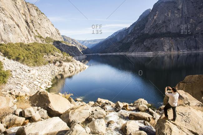 Caucasian man photographing lake in Yosemite National Park, California, United States