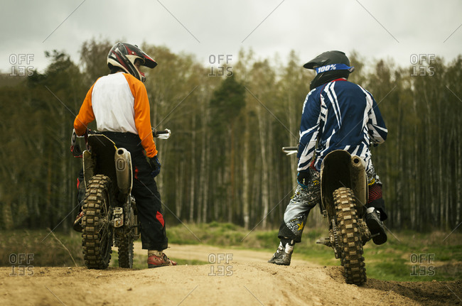 Caucasian men riding dirt bikes on road