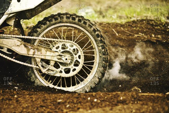 Dirt bike tire smoking in dirt