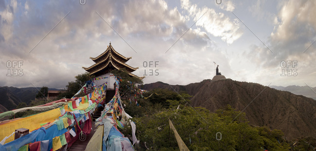Panoramic view of prayer flags and traditional building on mountain