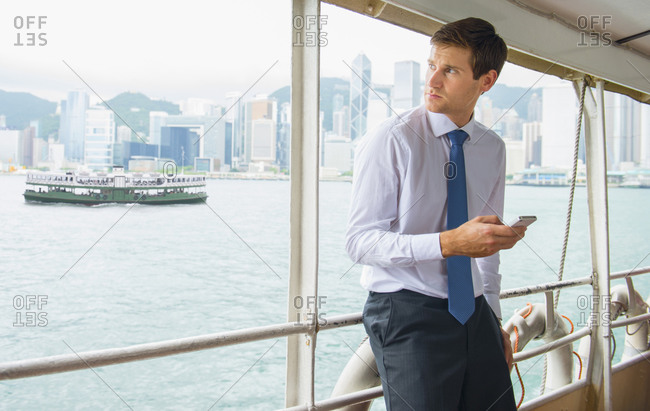 Caucasian businessman using cell phone on ferry