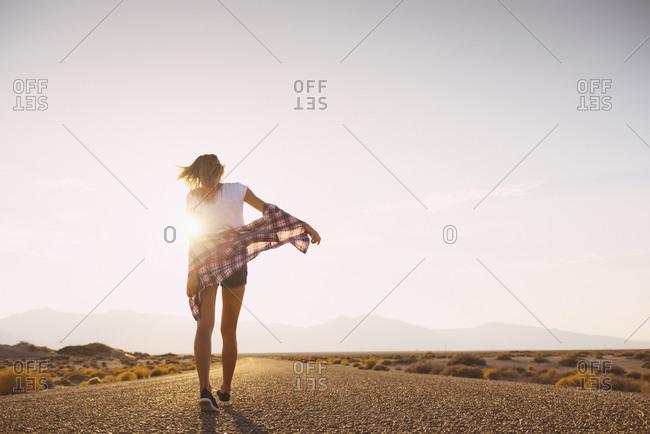 Hispanic woman walking on remote road