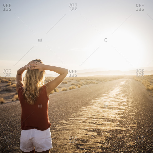 Hispanic woman walking on remote road