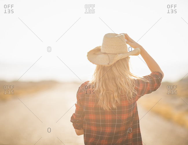 Hispanic woman holding hat on remote road