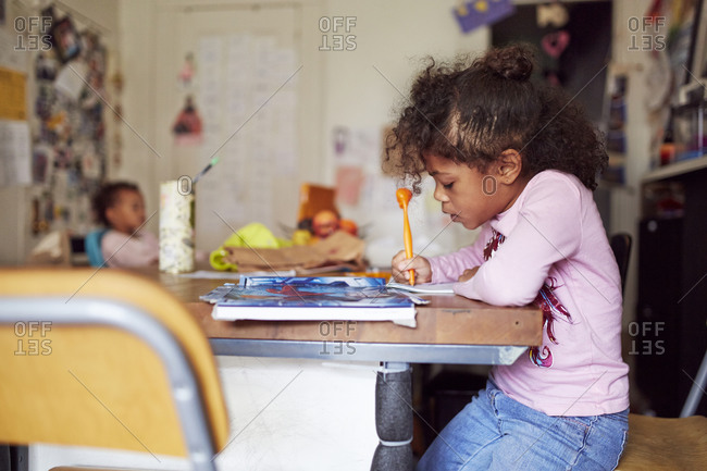 Mixed race girl drawing at table