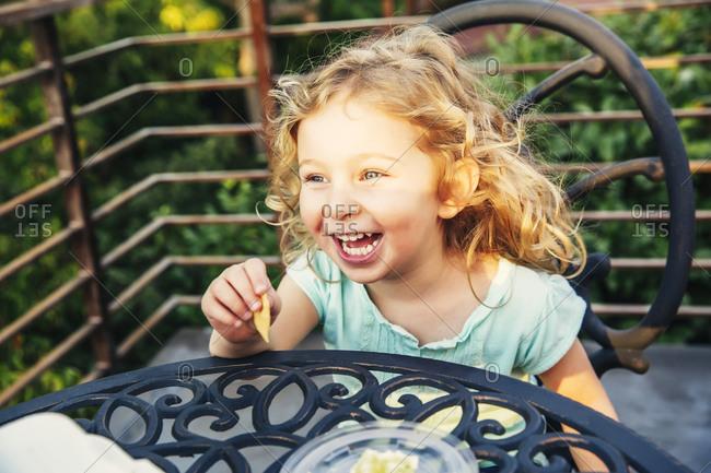 Caucasian girl eating on patio
