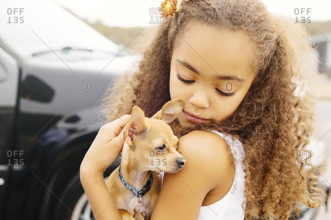 Mixed race girl petting dog outdoors