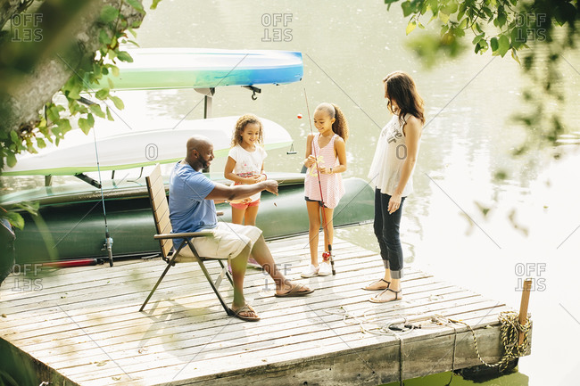 Family standing on dock in lake