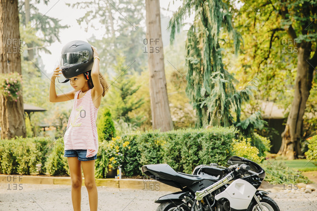 Mixed race girl putting on helmet