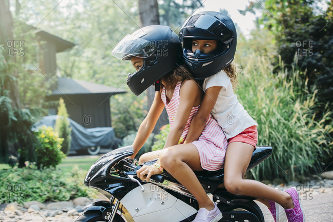 Mixed race sisters riding miniature motorcycle